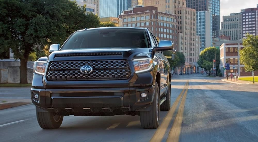 A black 2019 Toyota Tundra drives down an empty city street