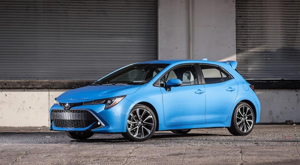 A bight blue 2019 Toyota Corolla sits in front of a dark warehouse