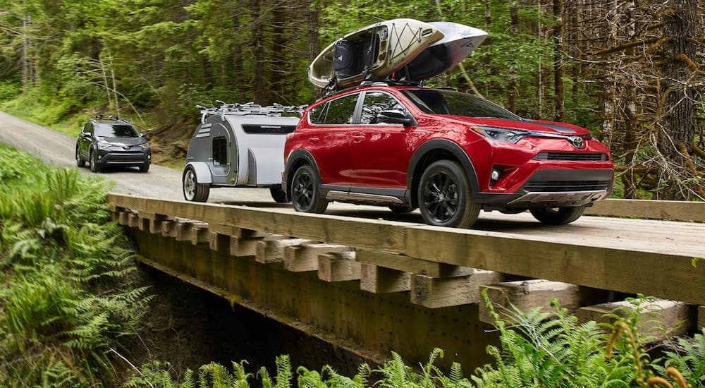 A red Toyota SUV with kayaks on the roof crosses a bridge on a camping trip