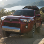 Red 2019 Toyota 4Runner with luggage on top climbing mountain with lake and mountains in background