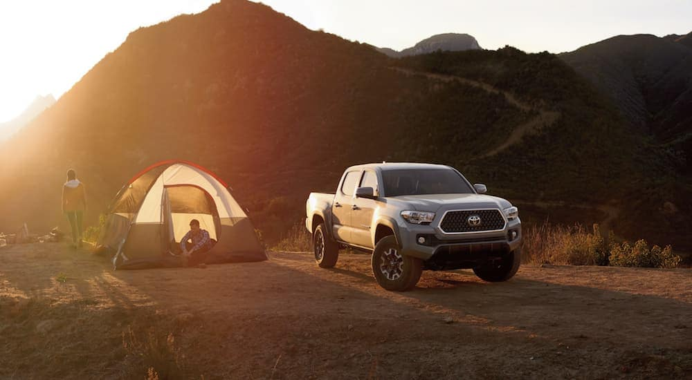 Gray Toyota Tacoma next to a tent in the mountains at sunset
