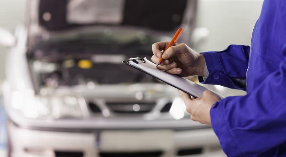 Mechanic in blue jumpsuit with clipboard, out of focus car in back