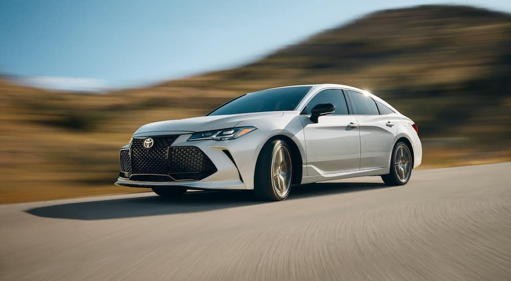 A white 2019 Toyota Avalon driving on a hilly road