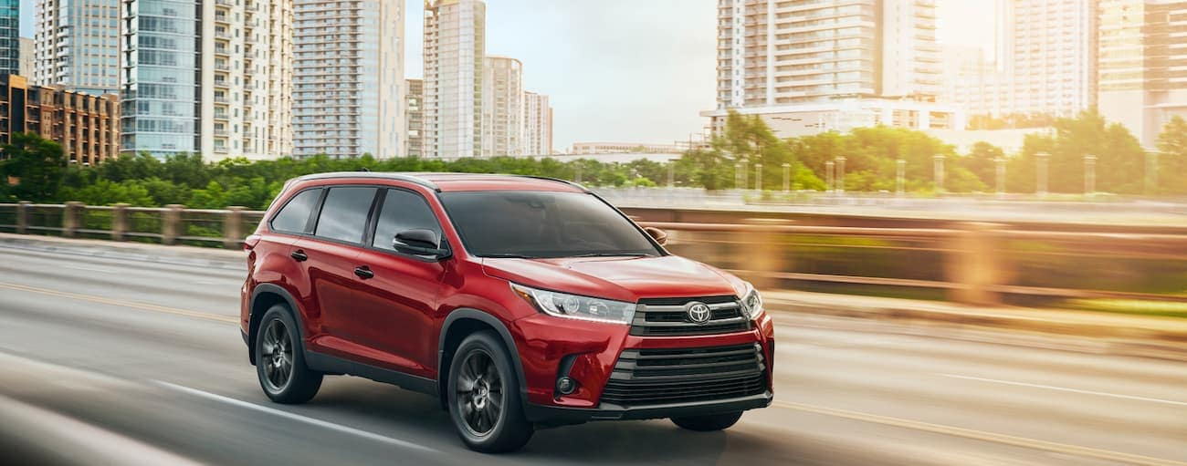 A red 2019 Toyota Highlander drives away from a city at sunset