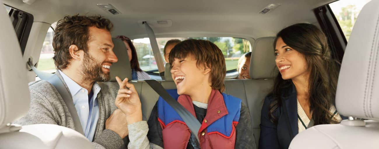 A family sits and laughs in the backseat of a 2019 Toyota Highlander