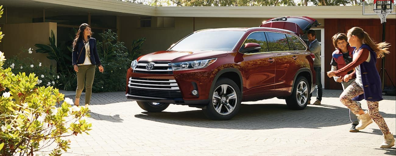 A family plays near a red 2019 Toyota Highlander parked in a driveway