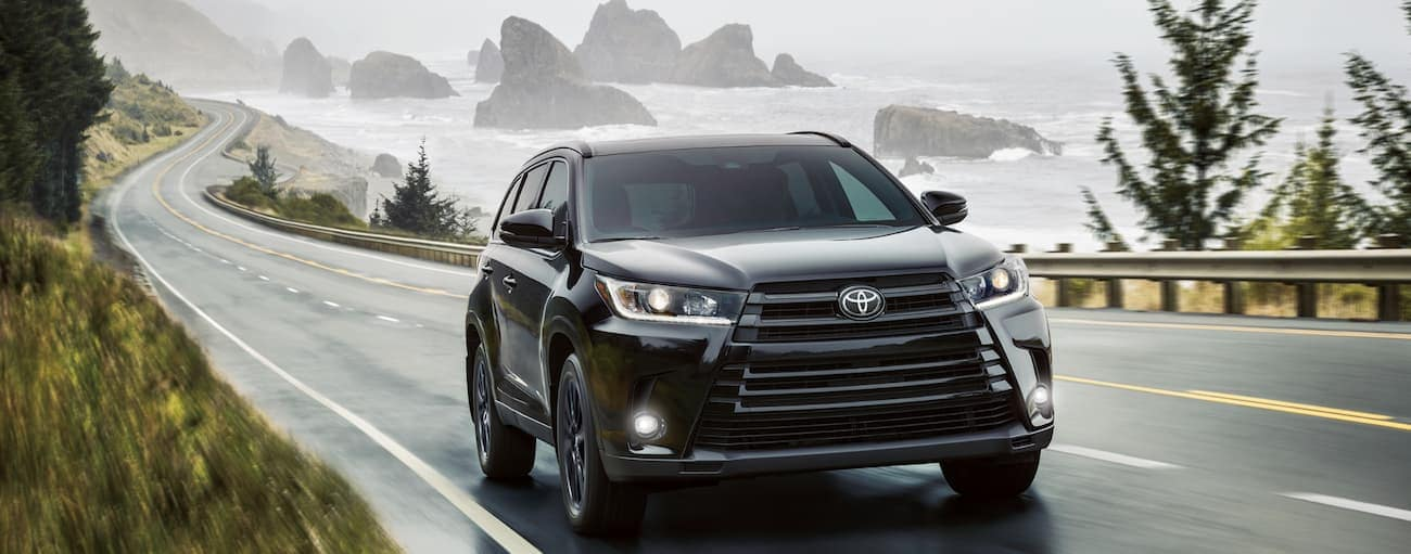 A black 2019 Toyota Highlander drives along a wet road alongside a body of water