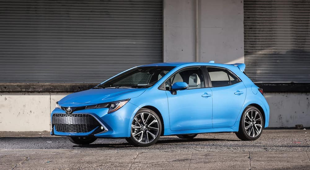 A bright blue new Toyota Corolla stands out against the bleak background of a concrete warehouse