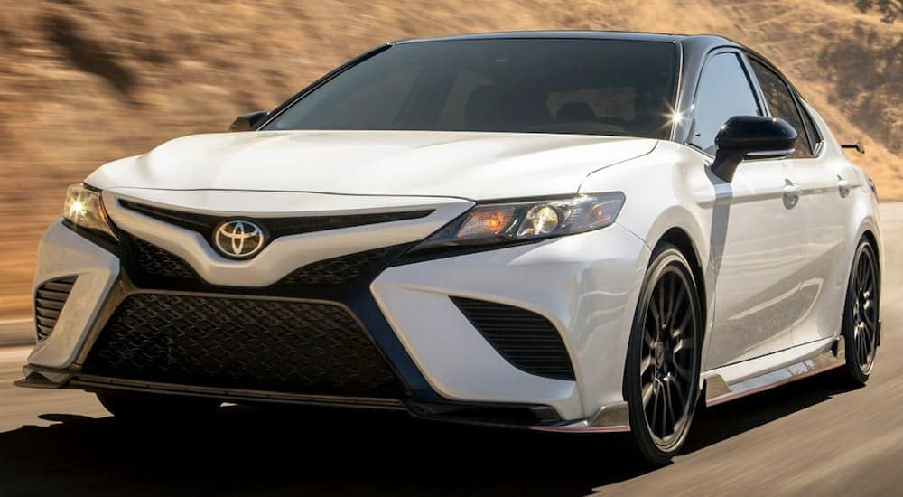 A white 2019 Toyota Camry cruises through hilly roads