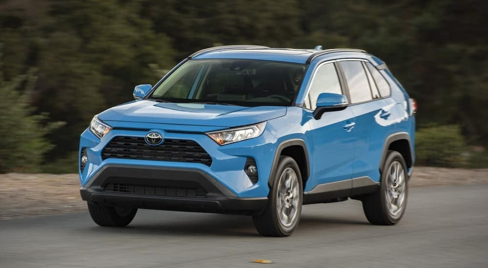 A new Toyota RAV4, blue, on driving on a road