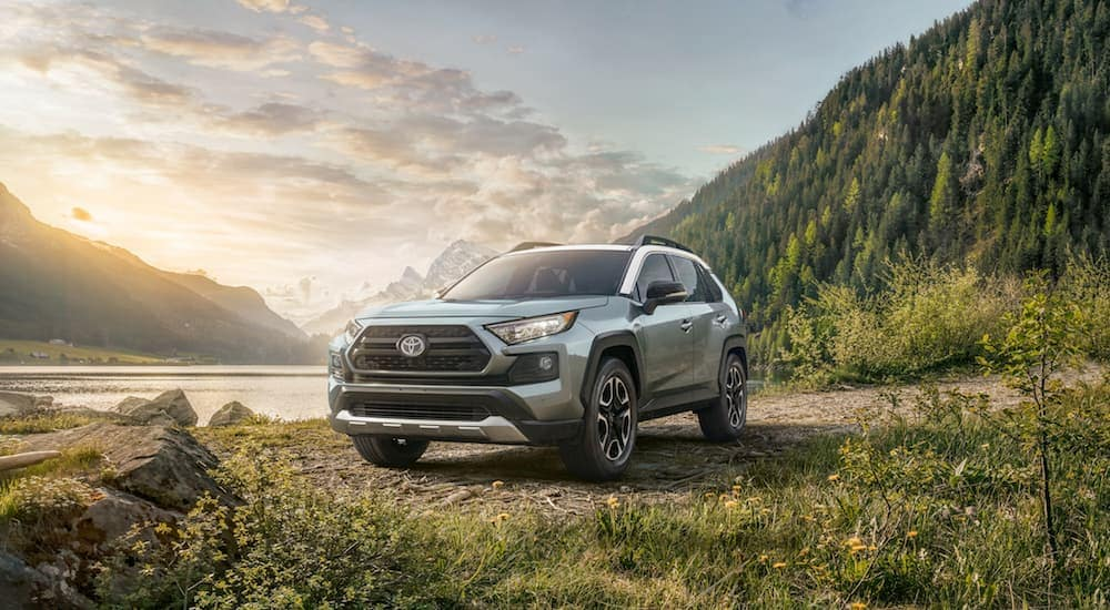 A mint colored 2019 Toyota Rav4 with mountains, trees and water in the back