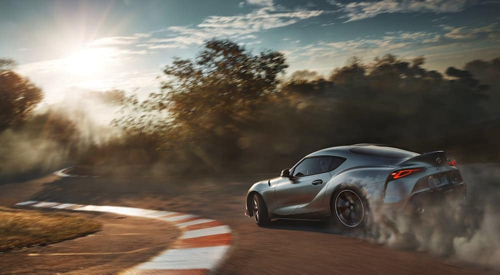 A silver 2020 Toyota Supra racing around a track at sunset