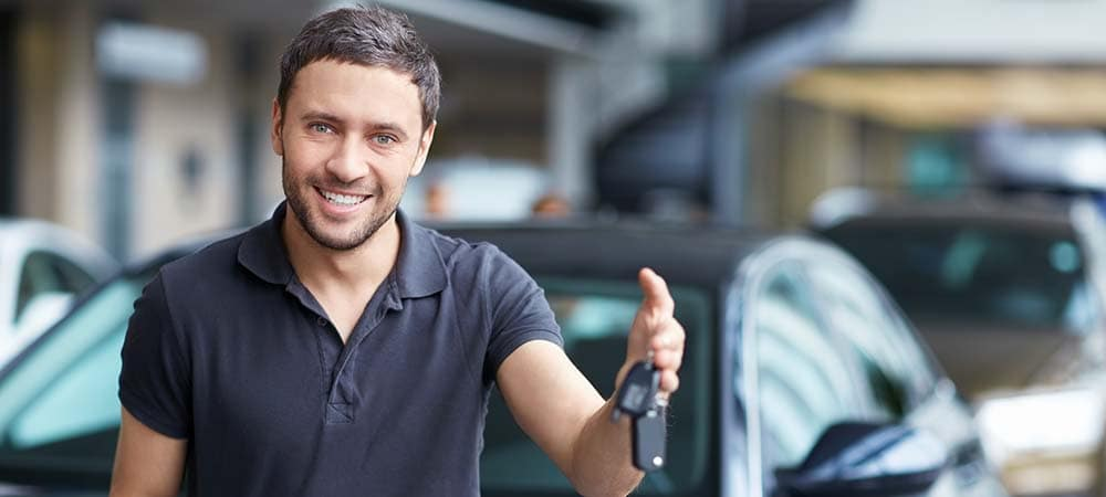 Young man holding the keys at the car to the car he bought