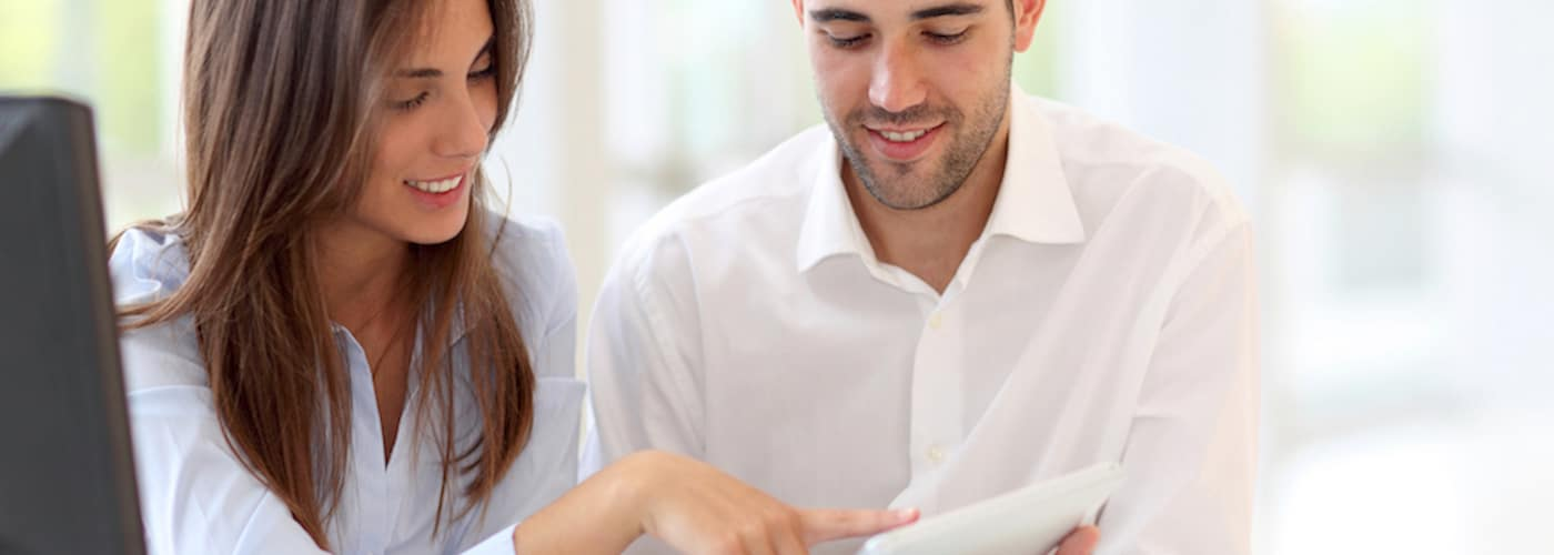 couple at home looking at touchpad together
