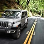 Image of a silver 2019 Jeep Wrangler driving on a forest highway.