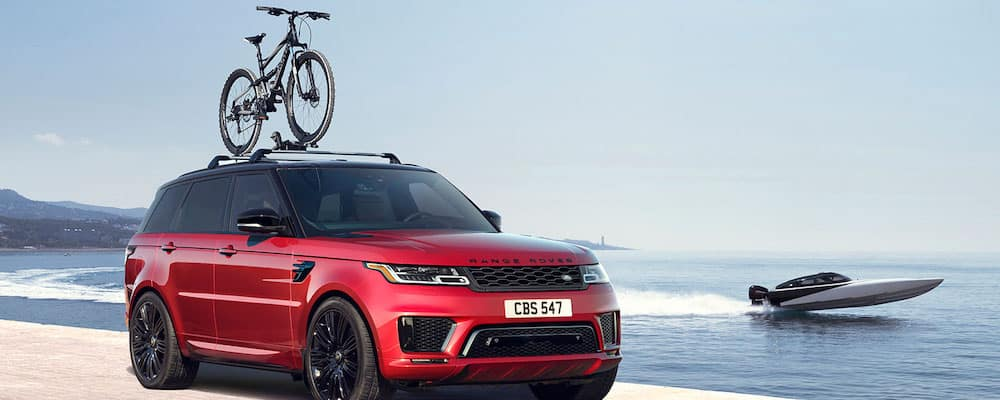 2019 Range Rover Sport in Firenze Red with bike rack and boat in background