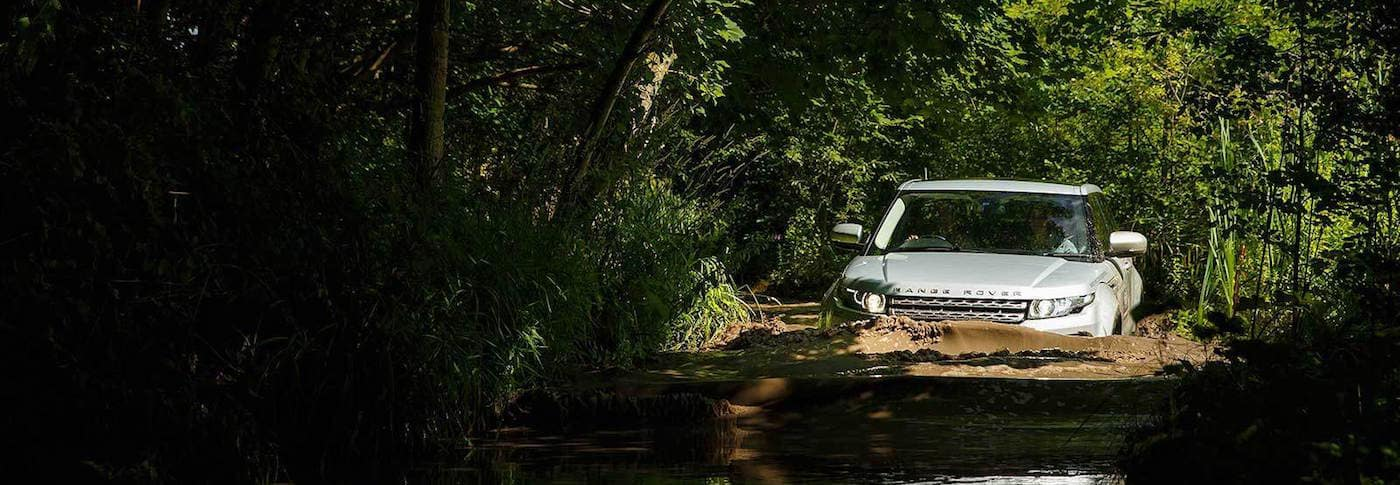 Range Rover wading in a river with trees surrounding