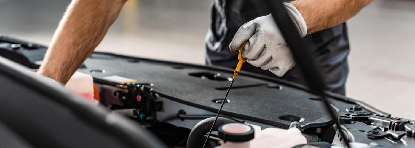 mechanic checking car oil level with dip stick