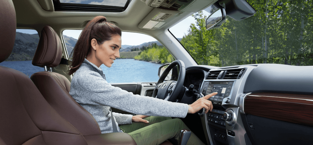 2020 Toyota 4Runner Interior first row seating with woman using infotainment system