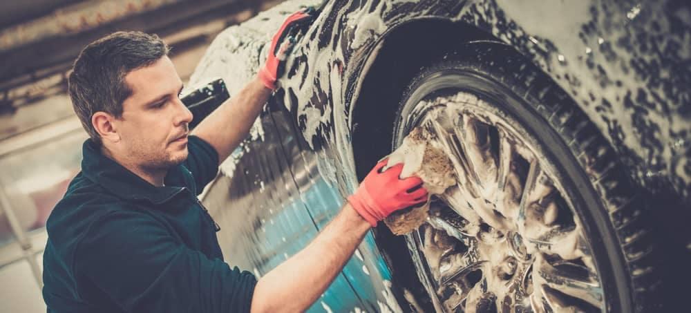 man washes wheel of vehicle