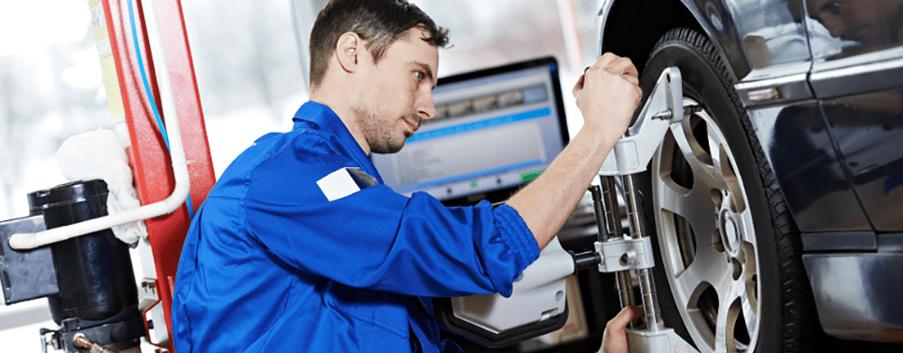 mechanic performs wheel alignment