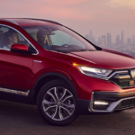 A 2020 Honda CR-V parked on a hill with a city in the background