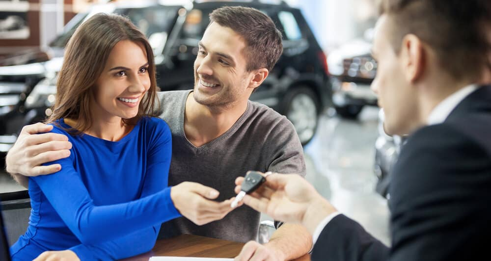 Car salesman giving the key of the new car to couple