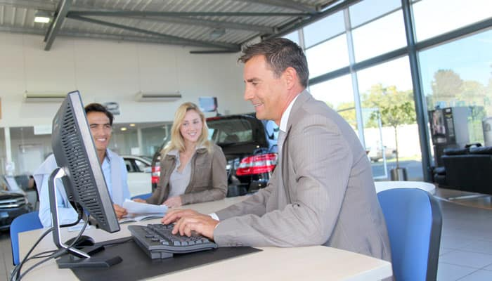 Couple Signing Contract at Dealership