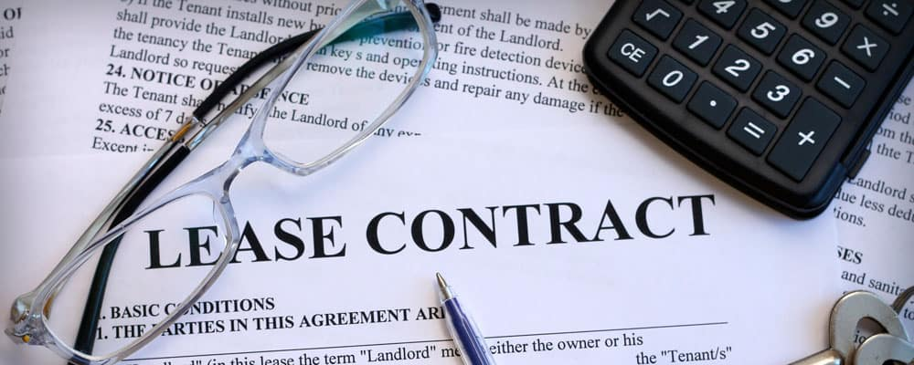 Leasing Contract on Table With Glass and Calculator
