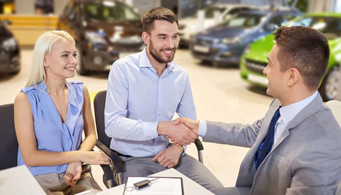 Happy Couple With Car Dealer Shaking Hands