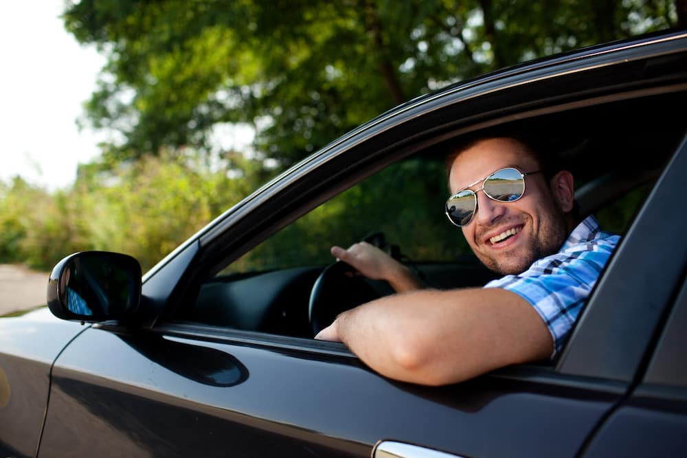 Young Man Smiling in a New Car