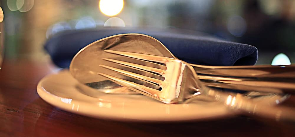 Silver fork and spoon sitting on a white plate in front of a blue napkin