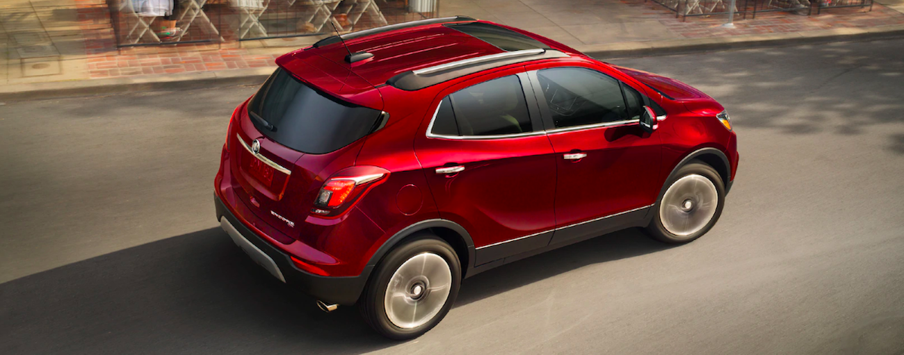 Red 2019 Buick Encore driving by cafe