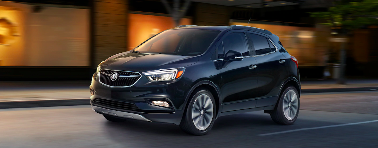 Black 2019 Buick Encore driving by building