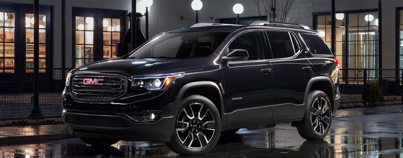 Black 2019 GMC Acadia at night in front of street lights