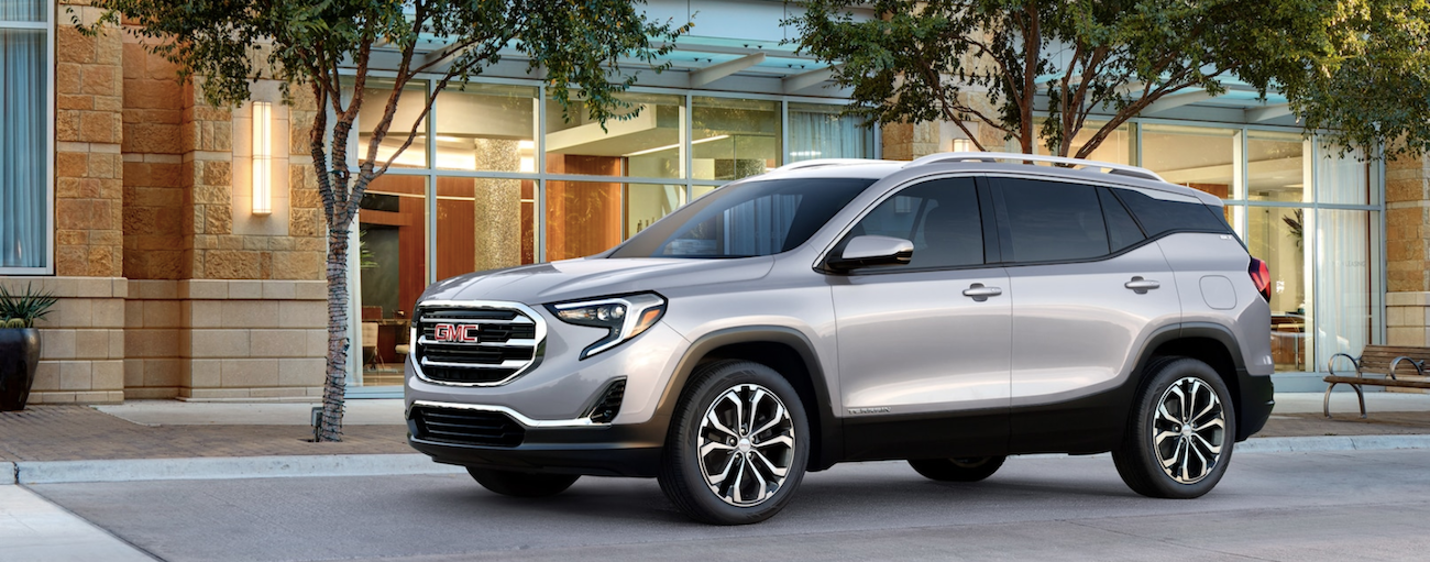 Gray 2019 GMC Terrain in front of stone building with trees
