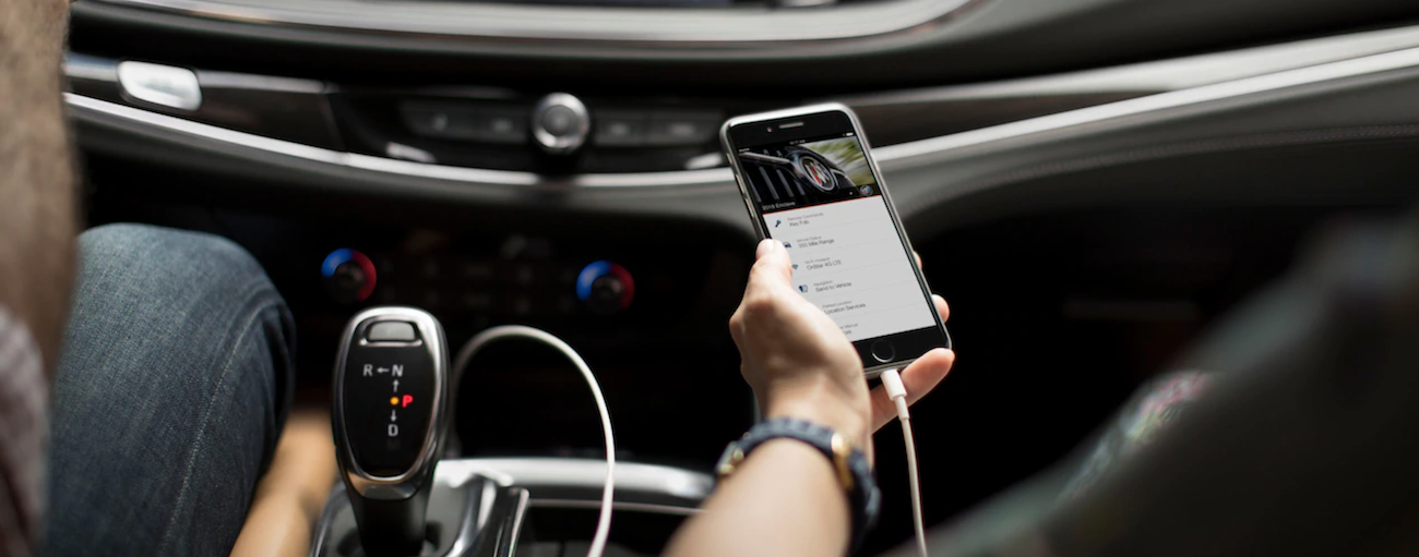Closeup of person holding phone plugged into 2019 Buick Enclave