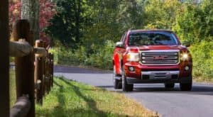 Red 2019 GMC Canyon driving down road with split log fence