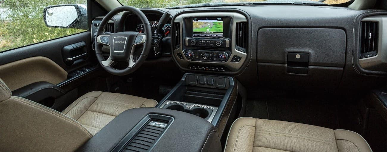 Black and tan leather interior of 2019 GMC Sierra Denali 2500HD in woods, view from passenger seat