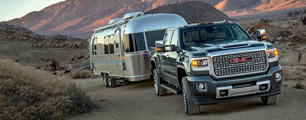 Black 2019 GMC Sierra Denali 2500HD towing trailer in desert with mountains in back, view from front