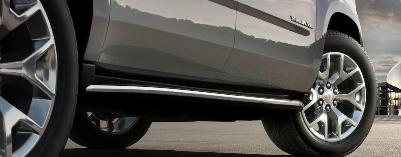 Closeup of grey 2019 GMC Yukon XL side step and wheels