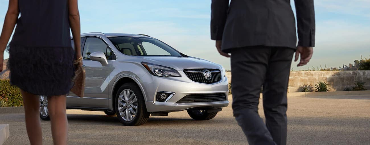 A man and woman walking away from the camera towards a silver 2019 Buick Envision