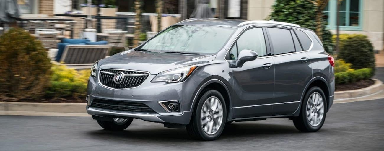 A gray/blue 2019 Buick Envision driving by an outdoor seating area