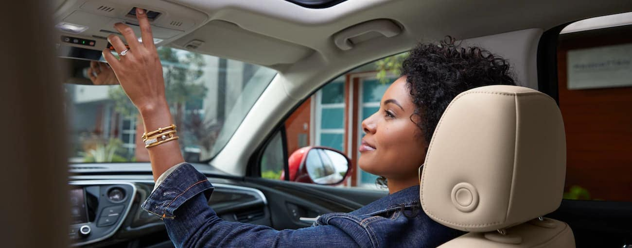 A woman pressing buttons inside a 2019 Buick Envision