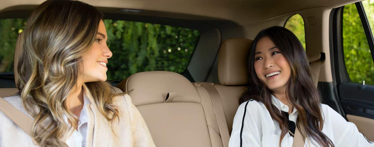 Two women sitting in the backseat of a 2019 Buick Envision