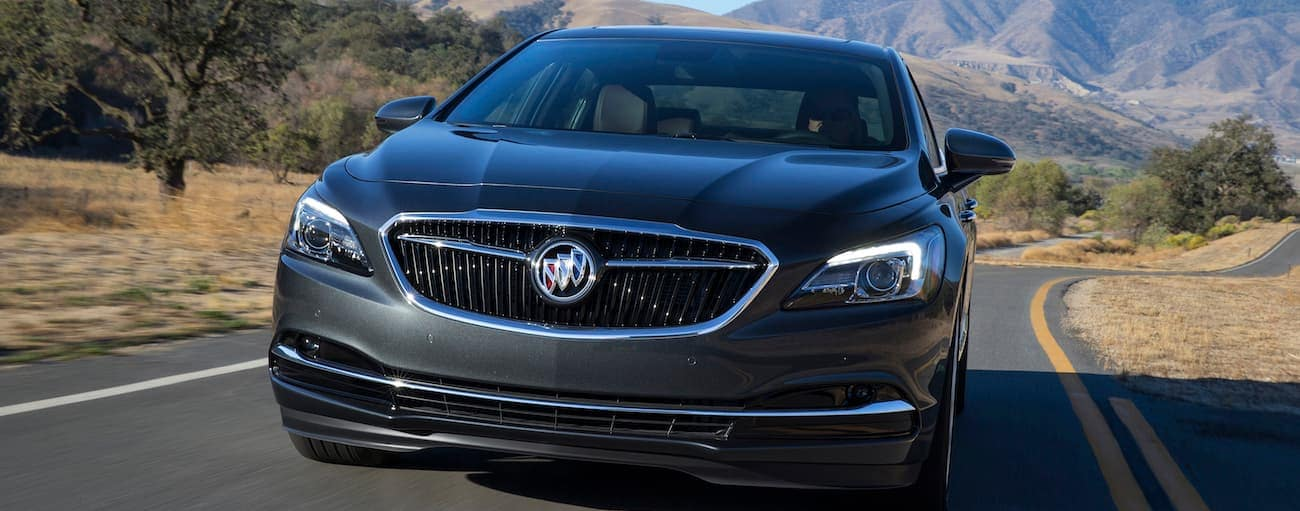 A black 2019 Buick LaCrosse driving along a road with mountains in the background