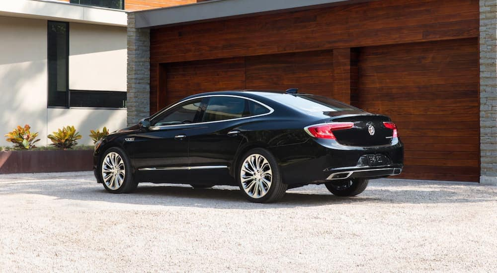 A black 2019 Buick LaCrosse in front of a garage with a wood face