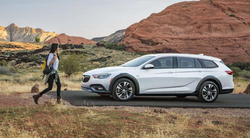 A woman walking towards a white 2019 Buick RegalX with mountains in the back