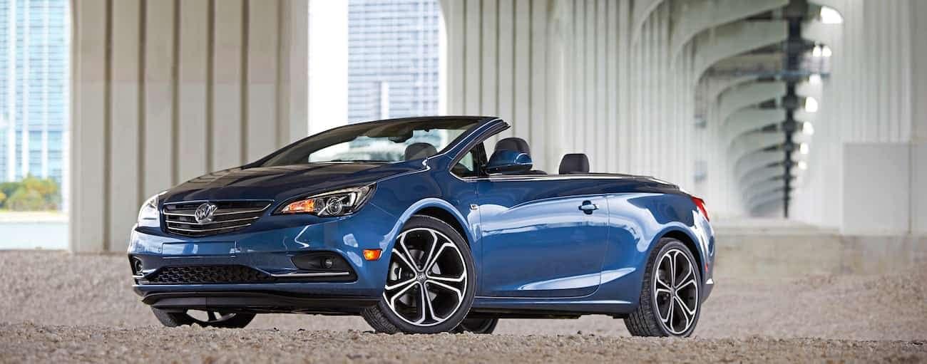 A blue 2019 Buick Cascada under a huge concrete highway overpass