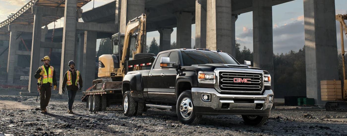 A black 2019 GMC Sierra 3500HD towing construction equipment